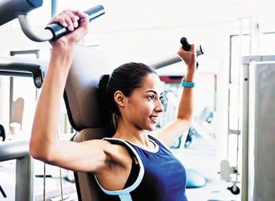 Junge Frau trainiert an der Schulterpresse im Fitnessstudio