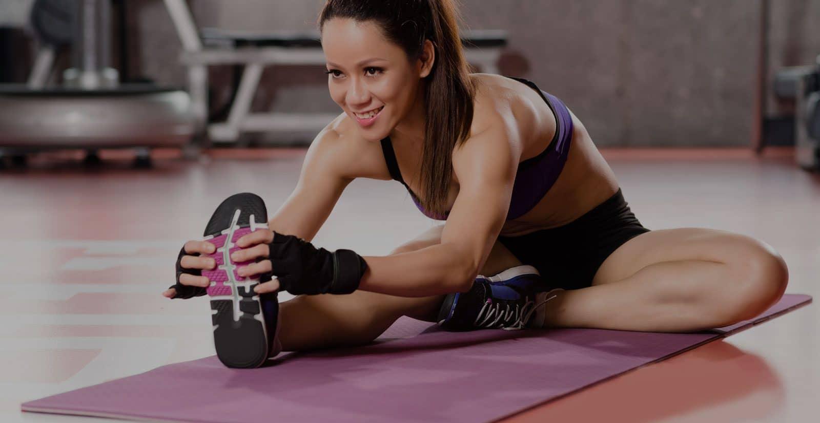 Junge trainierte Frau dehnt ihr Bein