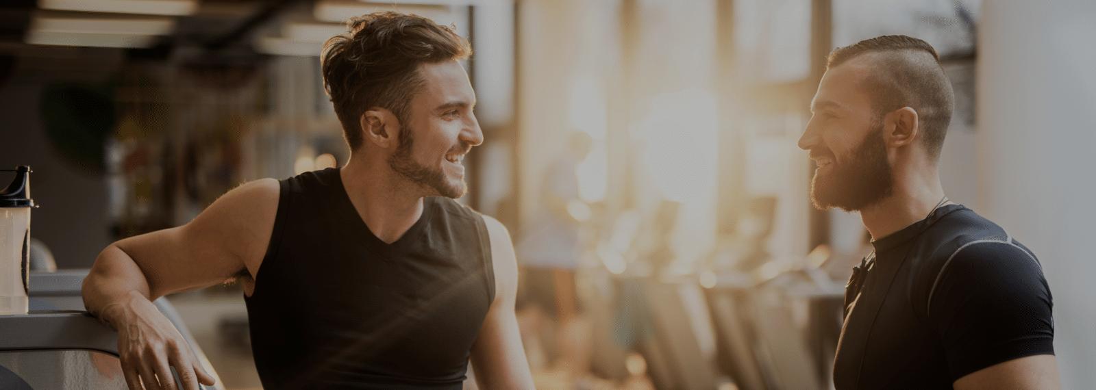 Zwei Männer unterhalten sich im Fitnessstudio