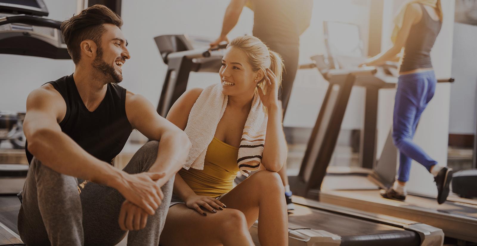 Junge Frau und junger Mann unterhalten sich im Fitnessstudio