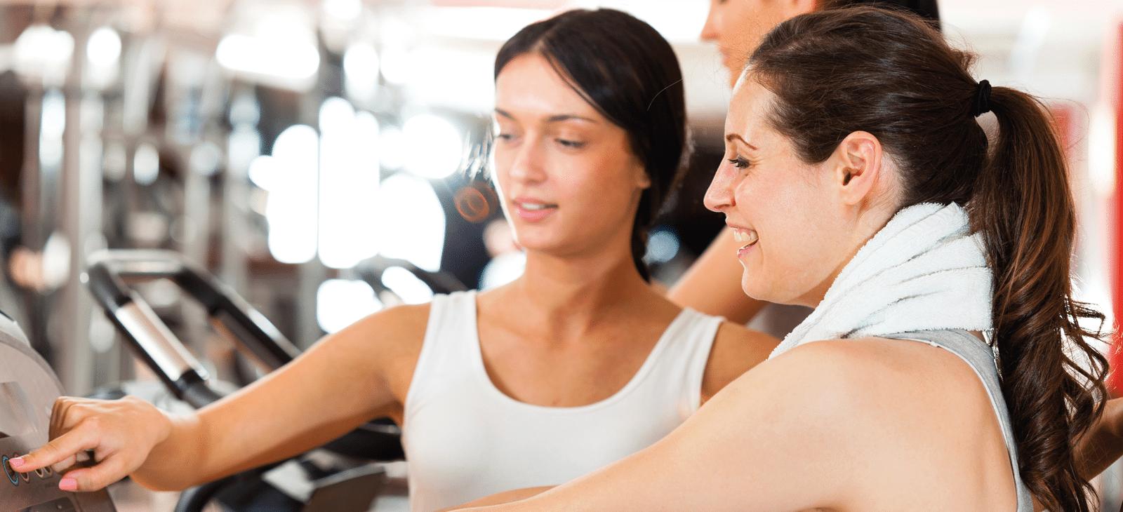 Trainerin im Fitnessstudio bei der Trainingseinweisung