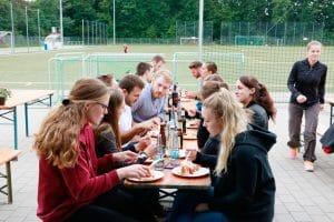 Sitzende Gruppe am Bierbanktisch die zusammen essen