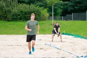 Ein Mann läuft im Sand und der andere Mann wirft mit der Hantel