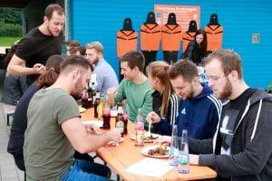 Viele Menschen sitzen auf einer Bierbankgarnitur und essen gesunde Lebensmittel