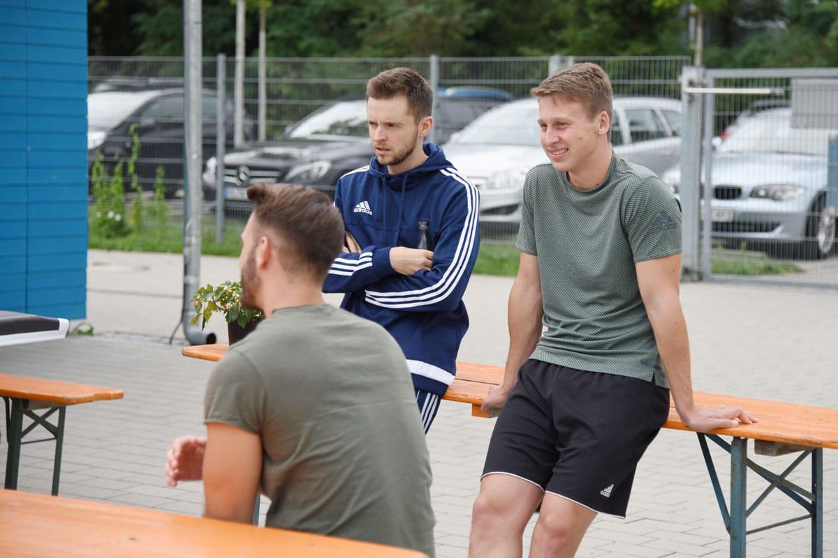 Zwei-trainierte-Männer-lehnen-an-Bierbanktisch-1200x800px