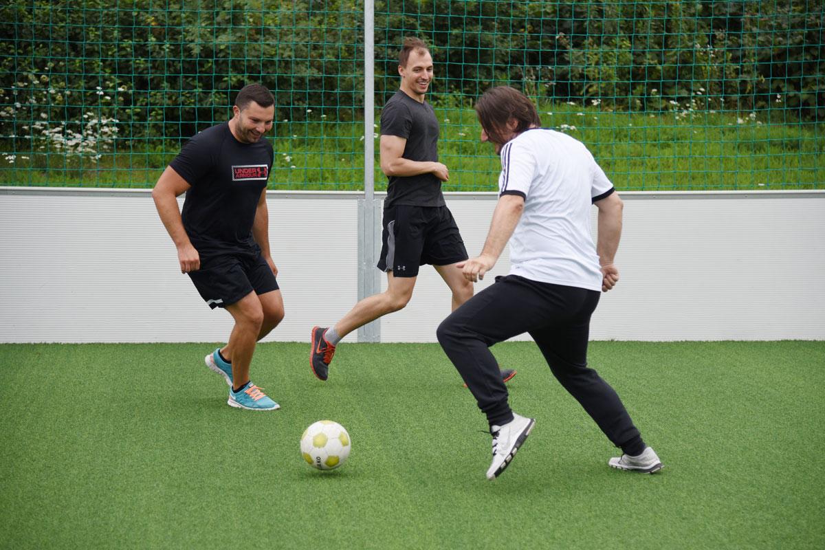 Drei-Männer-spielen-Fußball-1200x800px