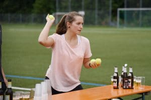 Eine Frau, die gerade einen Tennis-Ball mit der Hand wirft