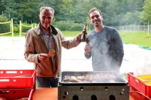 Zwei Männer vor einem Grill, stoßen mit einer Bierflasche in der Hand an.