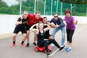 Gruppenfoto vom Team mit einem Bobbycar