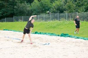 Trainer beim Hantel werfen in den Sand