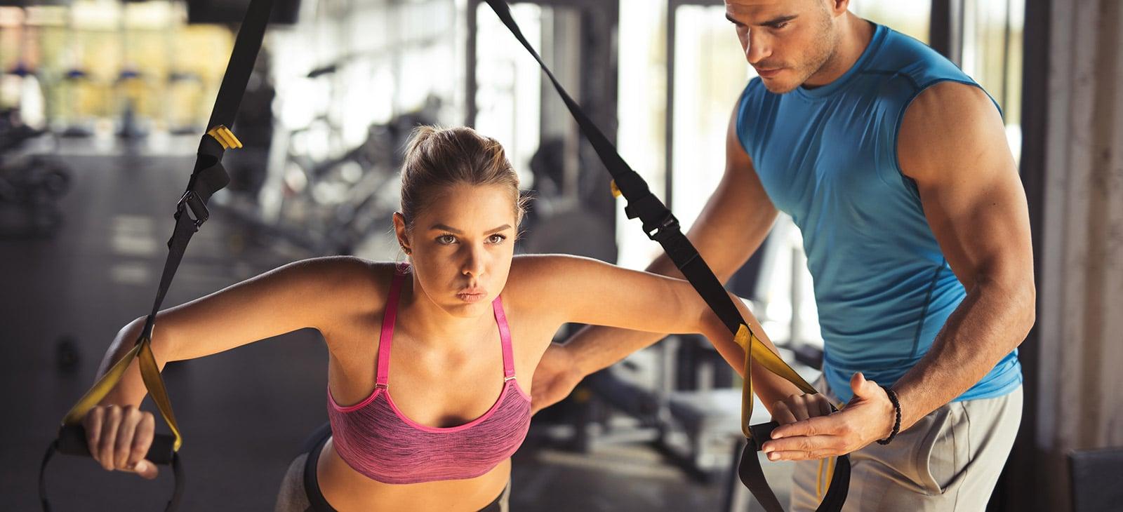 Frau trainiert mit TRX Bändern