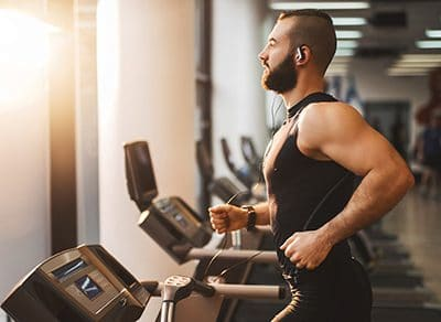 Mann trainiert auf dem Laufband im Fitnessstudio