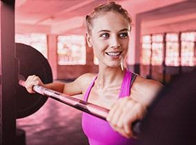 Für eine gute Figur trainiert Frau mit schweren Gewichten