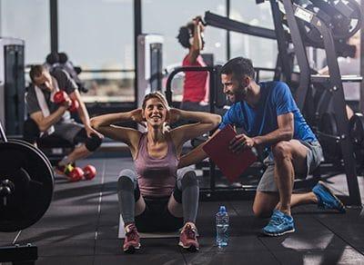 Ein Trainer zeigt wie die Fitnessübung richtig geht