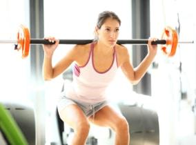 Junge Frau trainiert mit der Langhantel im Fitnesstdio
