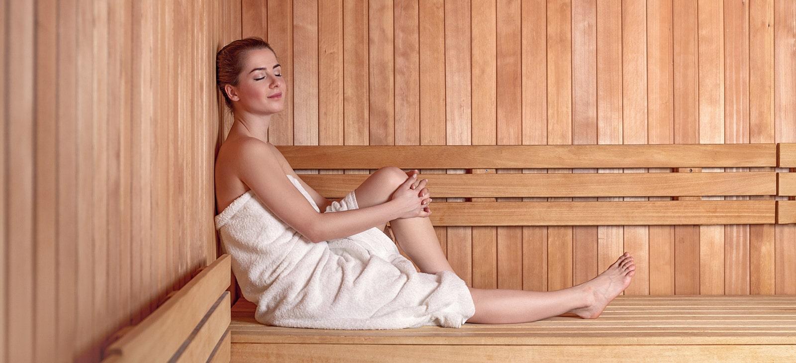 Junge Frau entspannt nach dem Fitnesstraining in der Sauna