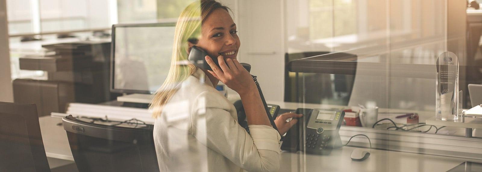 Junge Frau am Telefon im Fitness-Loft Callcenter