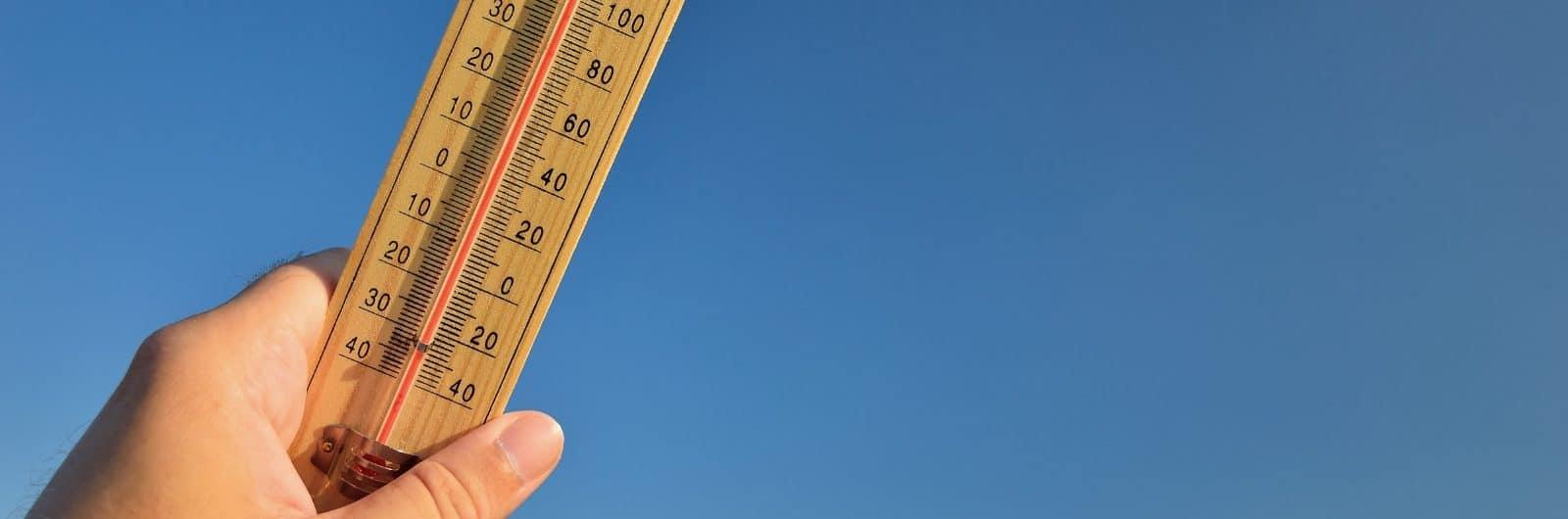 Sommerhitze: Thermometer und blauer Himmel