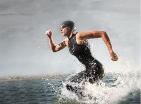 Eine Frau steigt aus dem Wasser beim Triathlon