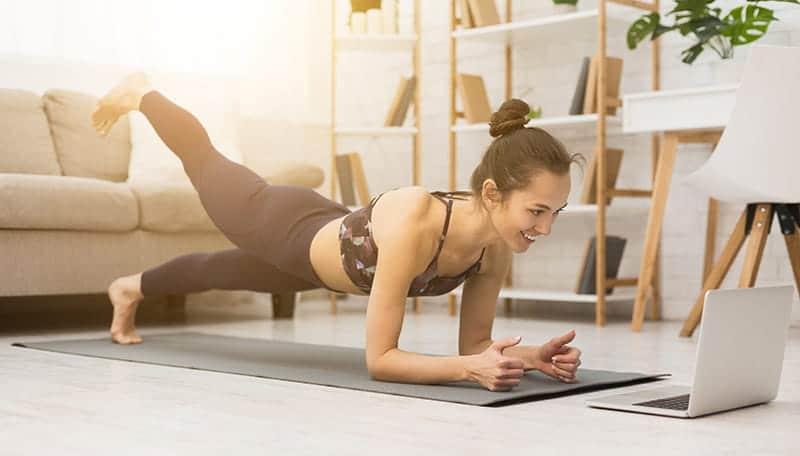 Junge Frau macht live Onlinekurse von Fitness-Loft