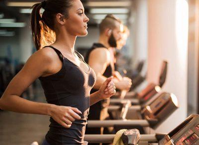 Junge Frau trainiert auf dem Laufband im Fitness-Loft